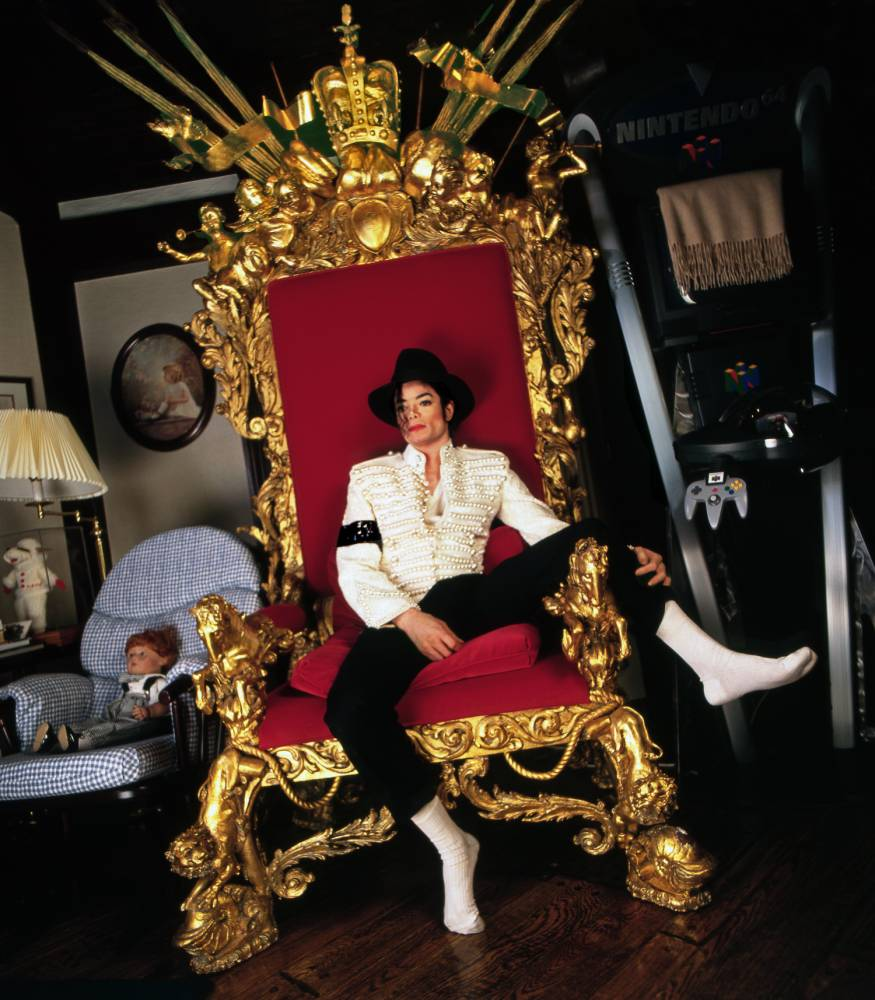 MJ New Throne Scan 10-09 Use@Benson  ALL PHOTOGRAPHS ©HARRY BENSON ARE FOR ONE TIME USE ONLY IN CONNECTION WITH THE MALLETT EXHIBITION.   Michael Jackson , Neverland, California, 1997. Fibre-based, archival pigment print © Harry Benson  'Although I had photographed Michael Jackson at his home Neverland before, this was the first time I had visited Neverland since Michael had become a father. I spent the day photographing Michael inside his home with his first born son Prince, and in his very own amusement park, with his beloved animals, and with the children of his employees. In Prince's bedroom, Michael held the baby in his arms, gave him a bottle, and sang to him until he fell asleep. Michael was very proud of his first-born son. In Michael's own bedroom, stood the red velvet chair. To me, the photograph represents the King of Pop sitting on his throne.'